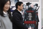 "People walk past a poster of the film ""Django Unchained"" outside a cinema in Beijing, April 11, 2013."