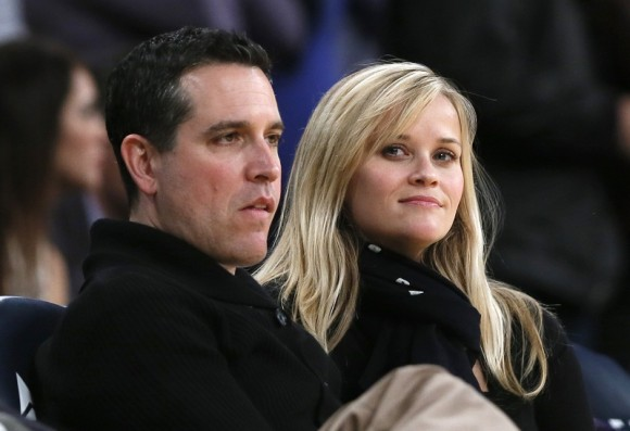 Actress Reese Witherspoon (R) and her husband Jim Toth watch the Toronto Raptors play the Los Angeles Lakers in their NBA basketball game in Los Angeles, March 8, 2013.