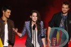 Actress Kristen Stewart (C) speaks, as actors Taylor Lautner (L) and Robert Pattinson