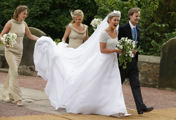 Melissa Percy is escorted by her father, Ralph Percy, the Duke of Northumberland, and bridesmaid Chelsey Davy (2nd L) as she arrives for her wedding to Thomas van Straubenzee, at St Michael's Church i