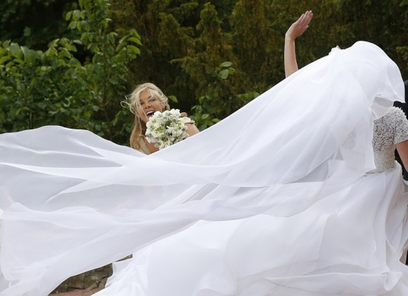 Bridesmaid Chelsy Davy reacts as wind blows the wedding dress of Melissa Percy as she arrives for her wedding to Thomas van Straubenzee, at St Michael's Church in Alnwick, northern England June 22, 20