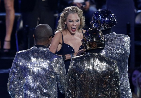"""Taylor Swift accepts the award for best female video for """"I Knew You Were Trouble"""" from presenters Daft Punk and Pharrell Williams (L) during the 2013 MTV Video Music Awar"""