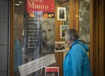 A customer looks at a window display congratulating Canadian author Alice Munro at bookstore Munro's Books after she won the Nobel Prize for Literature in Victoria, British Columbia October 10, 2013.