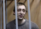 Dancer Pavel Dmitrichenko looks out from the defendant's holding cell during a hearing in Moscow in this October 22, 2013 file photo.