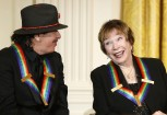 Carlos Santana (L) and fellow 2013 Kennedy Center Honors recipient Shirley MacLaine react to remarks by U.S. President Barack Obama (not pictured) during a reception at the White House in Washington D