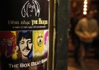 A fan walks near a poster promoting a tribute concert which marks the 32nd death anniversary of British legendary rocker John Lennon of the Beatles at a vintage cafe in Hanoi December 7, 2012.