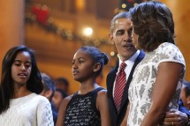 U.S. President Barack Obama (2nd R), his wife Michelle (R) and their daughters Malia (L) and Sasha (2nd L) join performers onstage to sing Christmas carols during a taping of the Christmas in Washingt