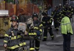 Fire fighters carry equipment away from the One World Trade Center in New York after responding to a fire in the tower on June 2, 2012.