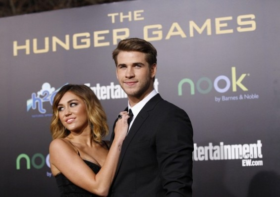 Cast member Liam Hemsworth poses with actress Miley Cyrus at the premiere of &#034;The Hunger Games&#034; at Nokia theatre in Los Angeles, California March 12, 2012.