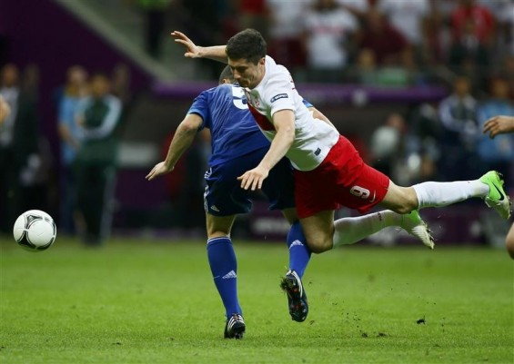 Poland's Robert Lewandowski (R) stumbles over Greece's Kyriakos Papadopoulos (L) during their Euro 2012 Group A match at the National Stadium in Warsaw, June 8, 2012.