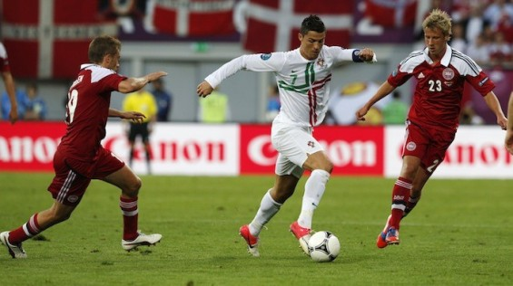 Portugal's Cristiano Ronaldo (C) runs with the ball as he is challenged by Denmark's Jakob Poulsen (L) and Tobias Mikkelsen during their Group B Euro 2012 soccer match at the New Lviv stadium in Lviv, June 13, 2012.