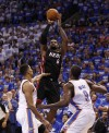 Miami Heat forward LeBron James (C) shoots over Oklahoma City Thunder guard Thabo Sefolosha (L) and forward Serge Ibaka in the fourth quarter during Game 2 of the NBA basketball finals in Oklahoma City, Oklahoma, June 14, 2012.