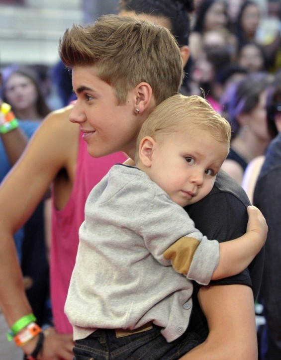 Singer Justin Bieber holds his brother Jaxon as they arrive on the red carpet during the MuchMusic Video Awards in Toronto June 17, 2012.