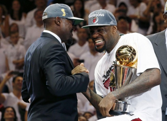 Miami Heat's LeBron James (R) celebrates with the Bill Russell NBA Finals MVP trophy after his team won the championship by defeating the Oklahoma City Thunder in Game 5 of the NBA basketball finals in Miami, Florida June 21, 2012.