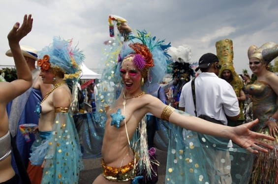 A woman poses for her friend before the start of the Mermaid Parade at Coney Island in the Brooklyn section of New York June 18, 2011.