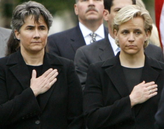 U.S. Vice President Dick Cheney's daughter Mary Cheney (2nd R) and her partner Heather Poe (2nd L) hold their hands over their hearts as an honor guard with the U.S. flag walks past during ceremonies in memory of the victims of the September 11 attac