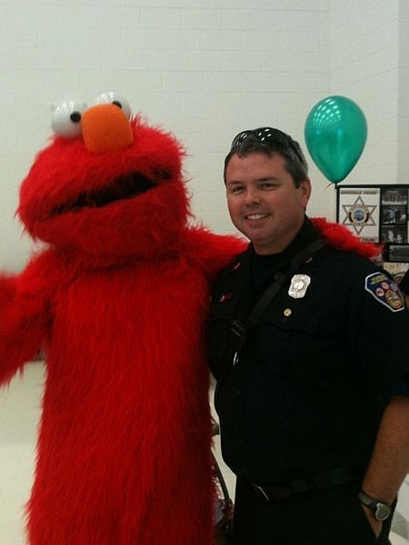 Elmo impersonator posing with a police officer