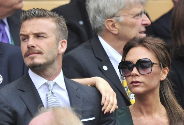 British soccer player David Beckham (L) sits with his wife Victoria Beckham