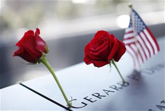 A pair of roses and a U.S. flag are left on one of the panels containing the names of the victims of the attacks on the first day that the 9/11 Memorial was opened to the public at the World Trade Center site in New York, September 12, 2011.