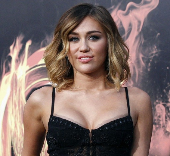 Actress Miley Cyrus poses at the premiere of &#034;The Hunger Games&#034; at Nokia theatre in Los Angeles, California March 12, 2012. The movie opens in the U.S. on March 23.
