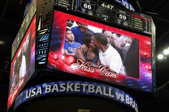 "U.S. President Barack Obama and first lady Michelle Obama are shown kissing on the ""Kiss Cam"" screen during a timeout in the Olympic basketball exhibition game between the U.S. and Brazil national men's teams in Washington, July 16, 2012."