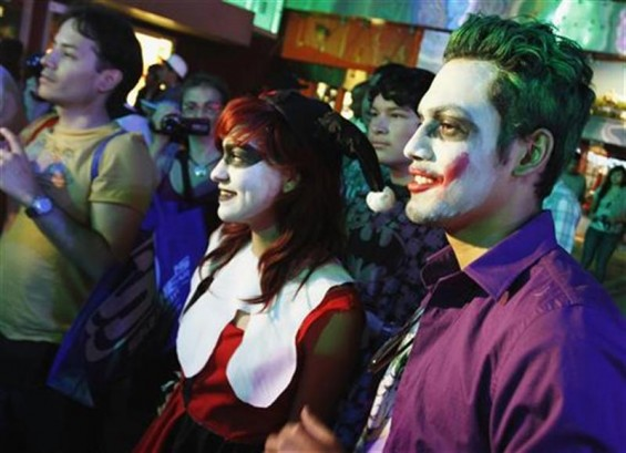 "People, dressed as characters from Batman movies, pose while waiting for the midnight premiere of ""The Dark Knight Rises"", the final installment of Christopher Nolan's Batman trilogy, in Universal Cit"