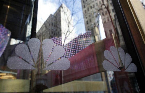 NBC logos are seen on a door with buildings around Rockefeller Center reflected in the background at the home of NBC&#039;s studios, in New York, December 3, 2009. 