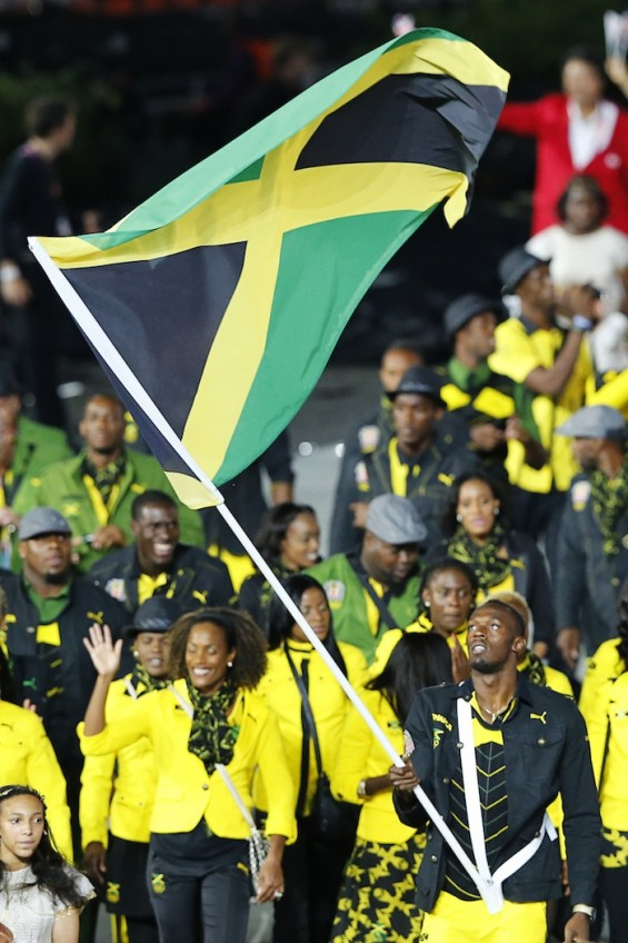 Jamaica's flag bearer Usain Bolt holds the national flag as he leads the contingent in the athletes parade during the opening ceremony of the London 2012 Olympic Games at the Olympic Stadium July 27,