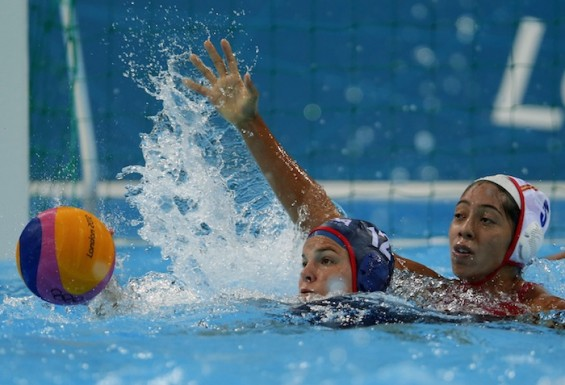 Annika Dries of the U.S. swims after the ball as Spain's Matilde Ortoz Reyes is seen behind her during their women's preliminary round Group A water polo match at the London 2012 Olympic Games at the