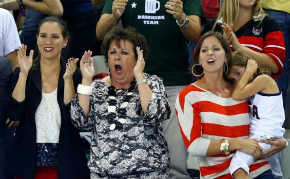 Debbie (C) and Whitney (R), the mother and sister respectively of swimmer Michael Phelps of the U.S., cheer Phelps on as he swims in the men's 200m individual medley final during the London 2012 Olymp