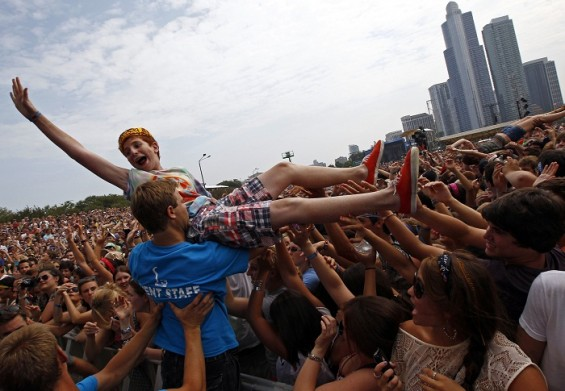 "A music fan crowd surfs during a performance by ""Foster the People"" at the Lollapalooza music festival in Grant Park in Chicago, August 5, 2011. The giant rock festival celebrating its 20th anniversar"