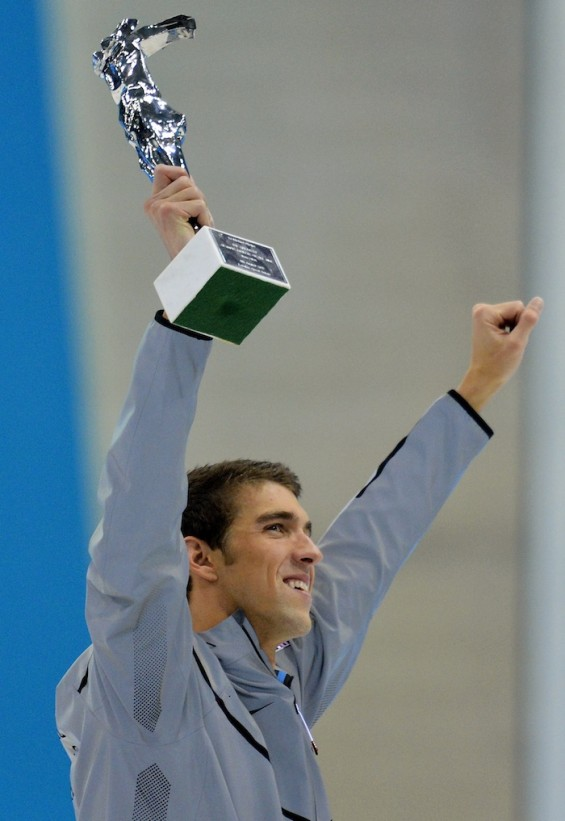 Michael Phelps of the U.S. holds up his award recognising him as the most decorated Olympian, during the London 2012 Olympic Games