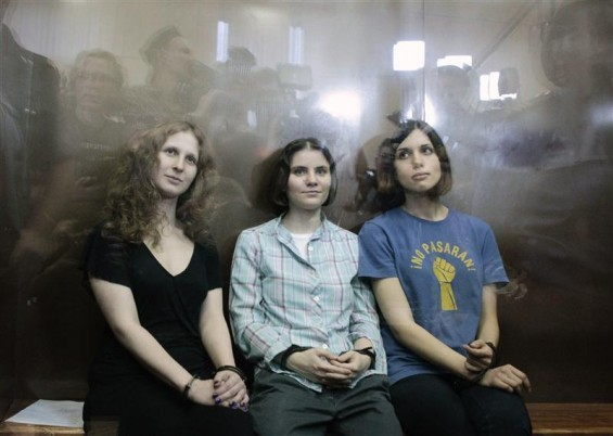 "Members of the female punk band ""Pussy Riot"" (R-L) Nadezhda Tolokonnikova, Yekaterina Samutsevich and Maria Alyokhina sit in a glass-walled cage after a court hearing in Moscow, August 17, 2012."