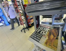 A man passes a newstand displaying copies of The Sun newspaper featuring a picture of a naked Prince Harry in London August 24, 2012.