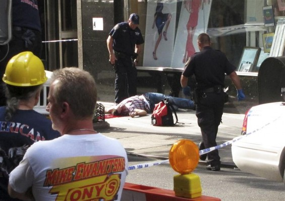 Bystanders and police look on as a man lies on the sidewalk after a shooting incident near the Empire State Building in New York August 24, 2012.