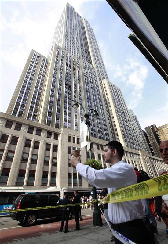 People watch and take photos at the scene of a shooting near the Empire State Building in New York, August 24, 2012. Two people were killed and at least eight were wounded in a shooting outside the la