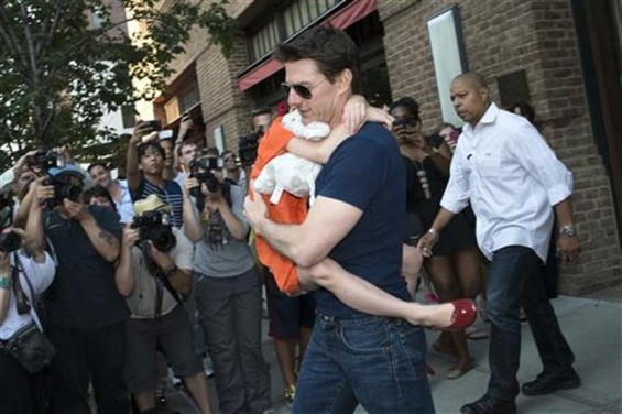 Actor Tom Cruise carries his daughter Suri past a group of photographers as they make their way from a hotel in New York, July 17, 2012.