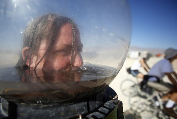 Hallie McConlogue stays cool partially submerged in a fishbowl helmet during the Burning Man 2012 &#034;Fertility 2.0&#034; arts and music festival in the Black Rock Desert of Nevada, August 31, 2012. 