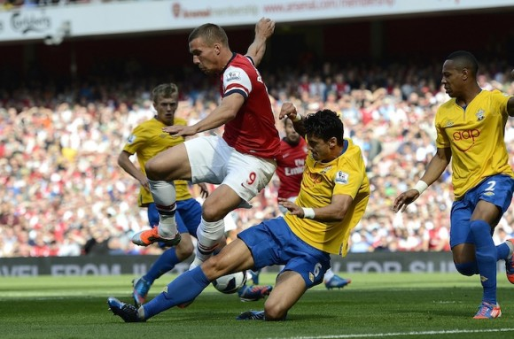 Arsenal's Lukas Podolski challenges Southampton's Jose Fonte during their English Premier League soccer match in London