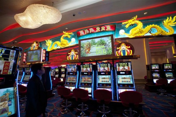 A man looks at a gaming machine inside a casino on the opening day of Sheraton Macao hotel at Sands Cotai Central in Macau September 20, 2012.