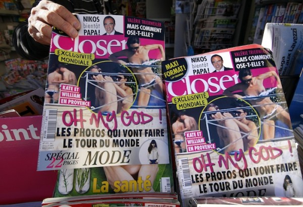 A man holds a copy of the French magazine Closer showing pictures of Catherine, Duchess of Cambridge, and Britain's Prince William are displayed in a newspaper kiosk in Nice