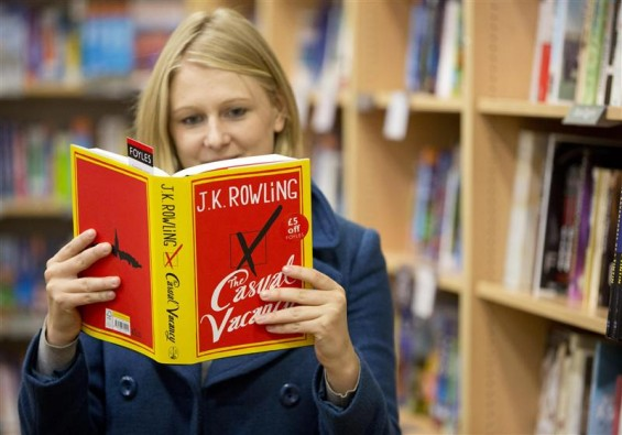 A woman poses with a copy of author J K Rowling's first adult fiction book The Casual Vacancy after it went on sale at a bookshop in central London, September 27, 2012.