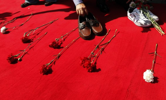 A participant lays a pair of shoes on a red carpet during an anti-gun rally on Individual Disarmament Day in central Istanbul September 28, 2012. A group of people who lost their relatives by gunfire