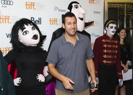 "Actor Adam Sandler poses with mascots of characters from ""Hotel Transylvania"", as he arrives on the red carpet for the film's gala presentation at the 37th Toronto International Film Festival, Septemb"