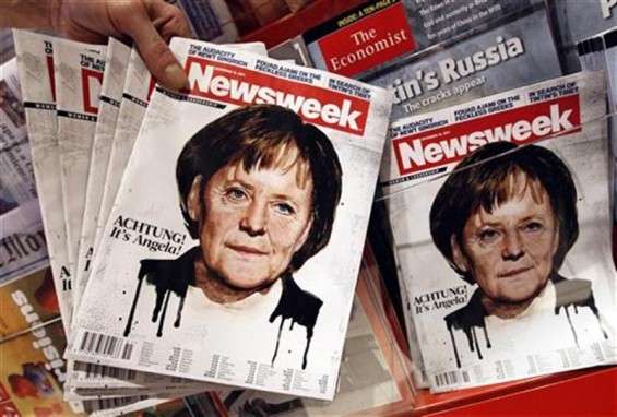 An employee of a store holds up copies of a Newsweek magazine bearing a picture of German Chancellor Angela Merkel for the photographer at the main train station in Berlin December 13, 2011.