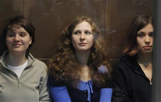 "Members of the female punk band ""Pussy Riot"" (L-R) Yekaterina Samutsevich, Maria Alyokhina and Nadezhda Tolokonnikova sit in a glass-walled cage before a court hearing in Moscow October 10, 2012."