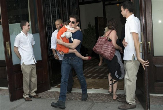 Actor Tom Cruise carries his daughter Suri as they make their way from a hotel in New York, July 17, 2012.