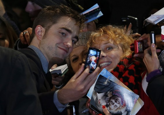 "Actor Robert Pattinson poses for a photo with a fan as he arrives for the European premiere of ""The Twilight Saga: Breaking Dawn Part 2"" in London November 14, 2012."