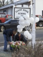 Volunteer firefighters place donated flowers at a makeshift memorial at the Sandy Hook Elementary School after a mass shooting in Newtown, Connecticut