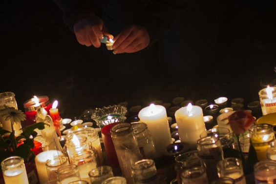 A girl lights a candle at a memorial for victims who died in the December 14 shootings at Sandy Hook Elementary School in Sandy Hook village in Newtown, Connecticut, December 17, 2012. 